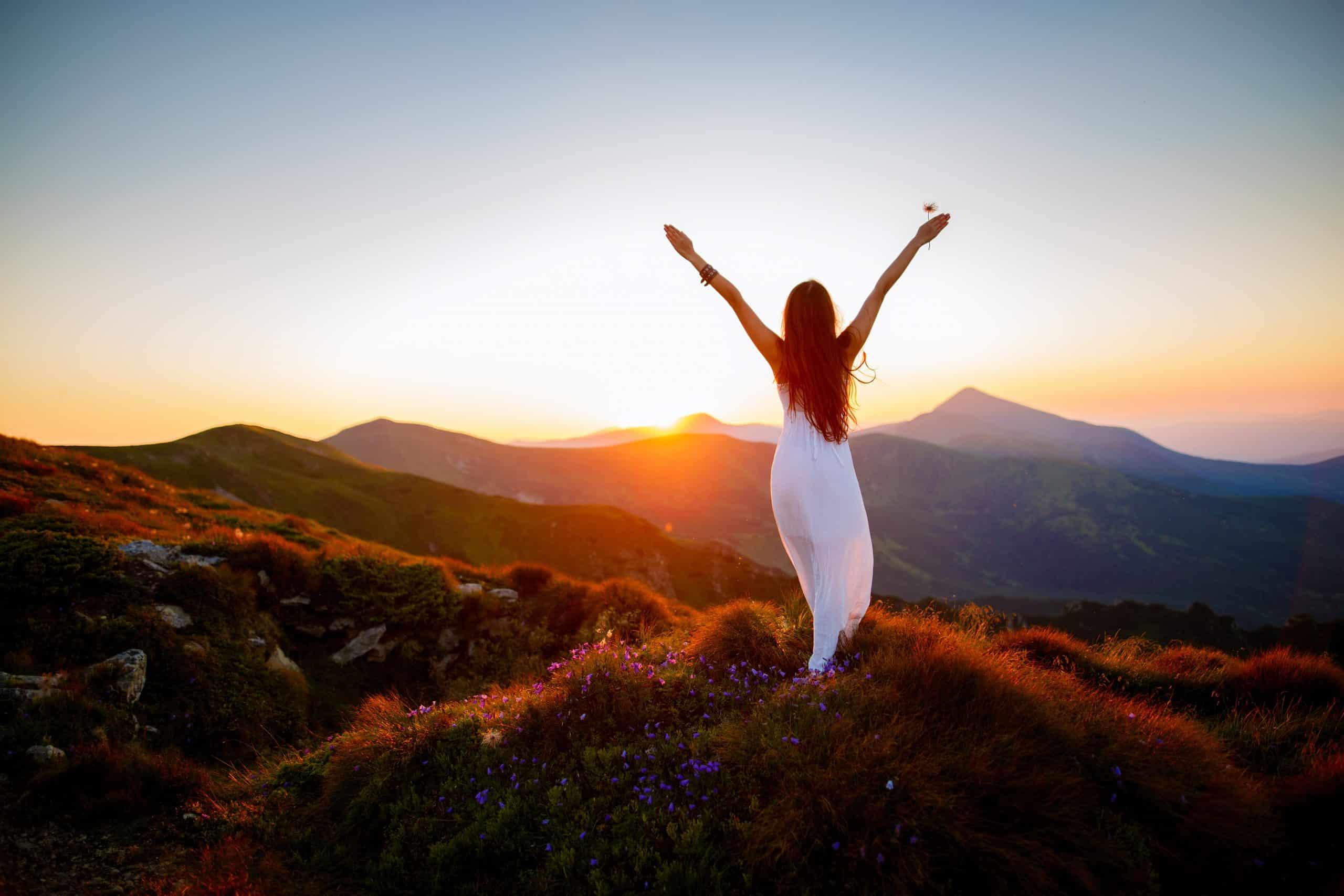 Bild Frau auf Berg mit nach oben gereckten Händen
